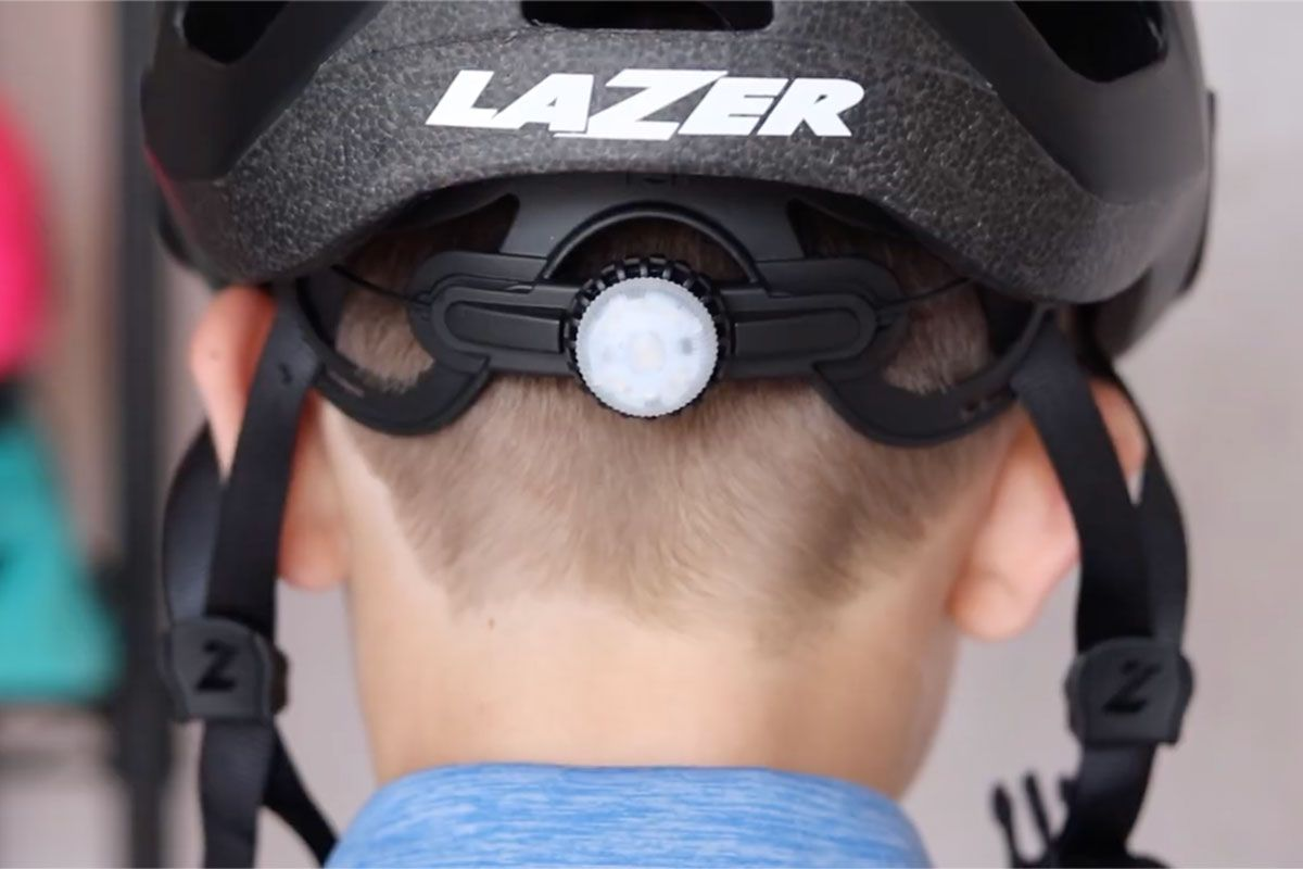 Back of a kid helmet on a child's head showing the dial adjust knob to get the right size