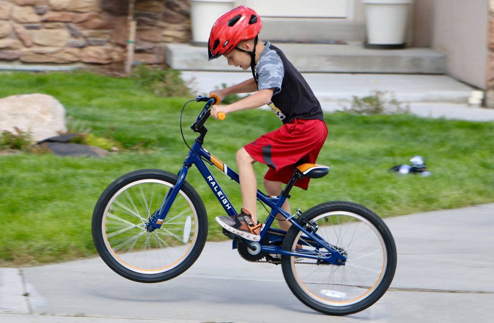 7-year-old riding the Raleigh MXR 20 kid's bike on the driveway
