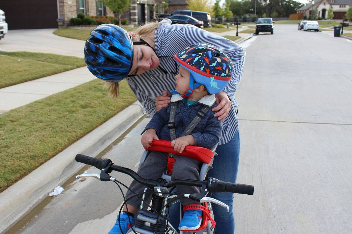 Mom smiling with 15-month-old boy in Peg Perego Orion child bike seat