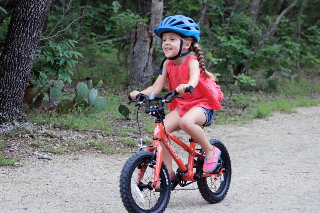 3 year old child smiling on a kids 14 inch bike