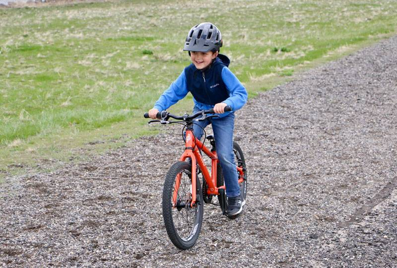 7 year old riding the pello rover 20 inch kids bike on gravel