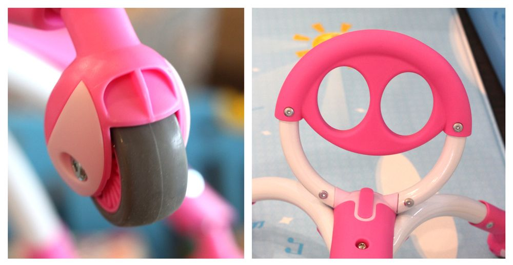 "Upclose shot of rubber caster wheel on Pewi, and the round ""handlebar"" that looks like a smiling face."