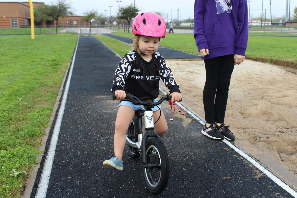 2 year old riding the Prevelo Alpha Zero balance bike down a black track