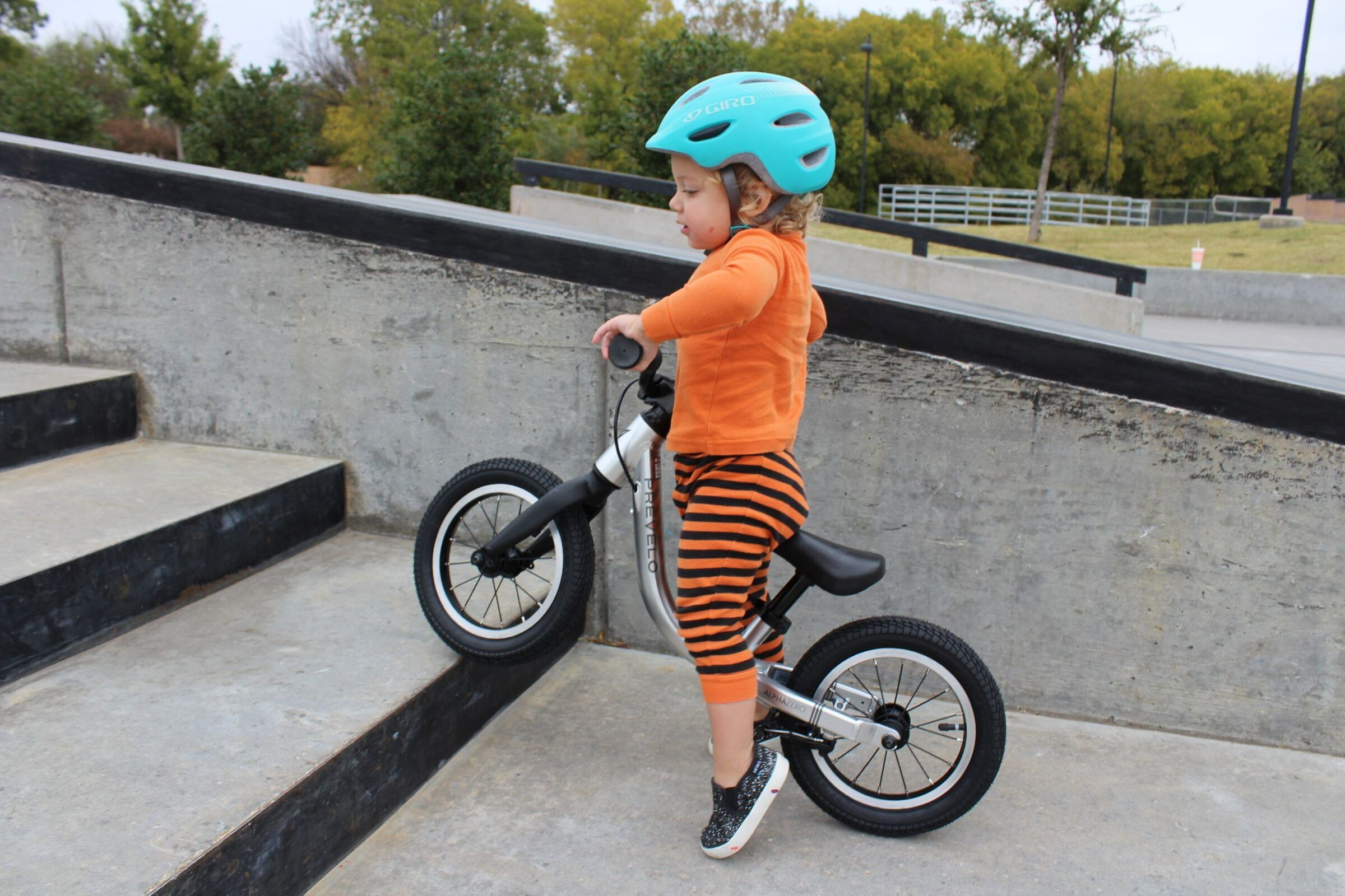 Toddler in halloween pjs lifting the Prevelo Alpha Zero Balance bike up the stairs at the skatepark.