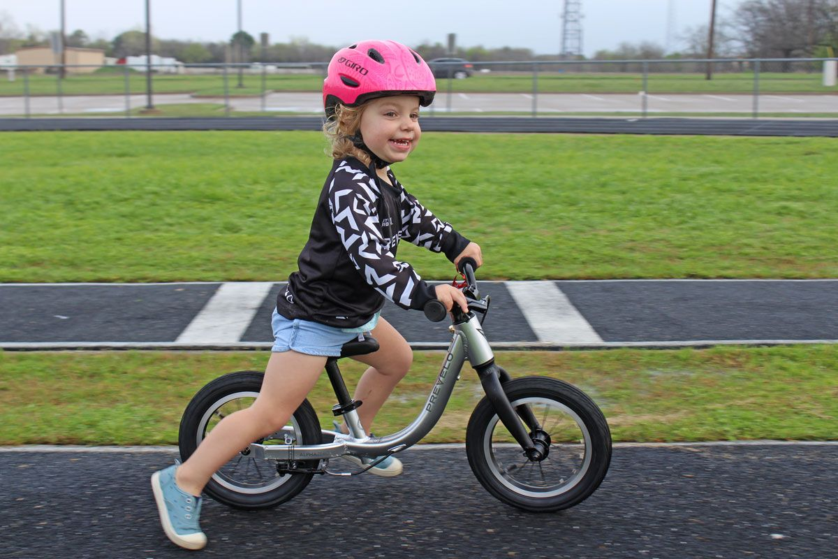 2 year old toddler riding Prevelo Alpha Zero balance bike at the school track and grinning