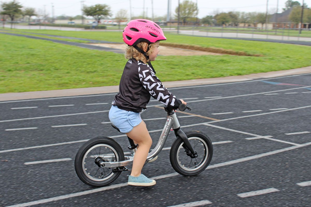 2 year old toddler riding Prevelo Alpha Zero balance bike at the school track
