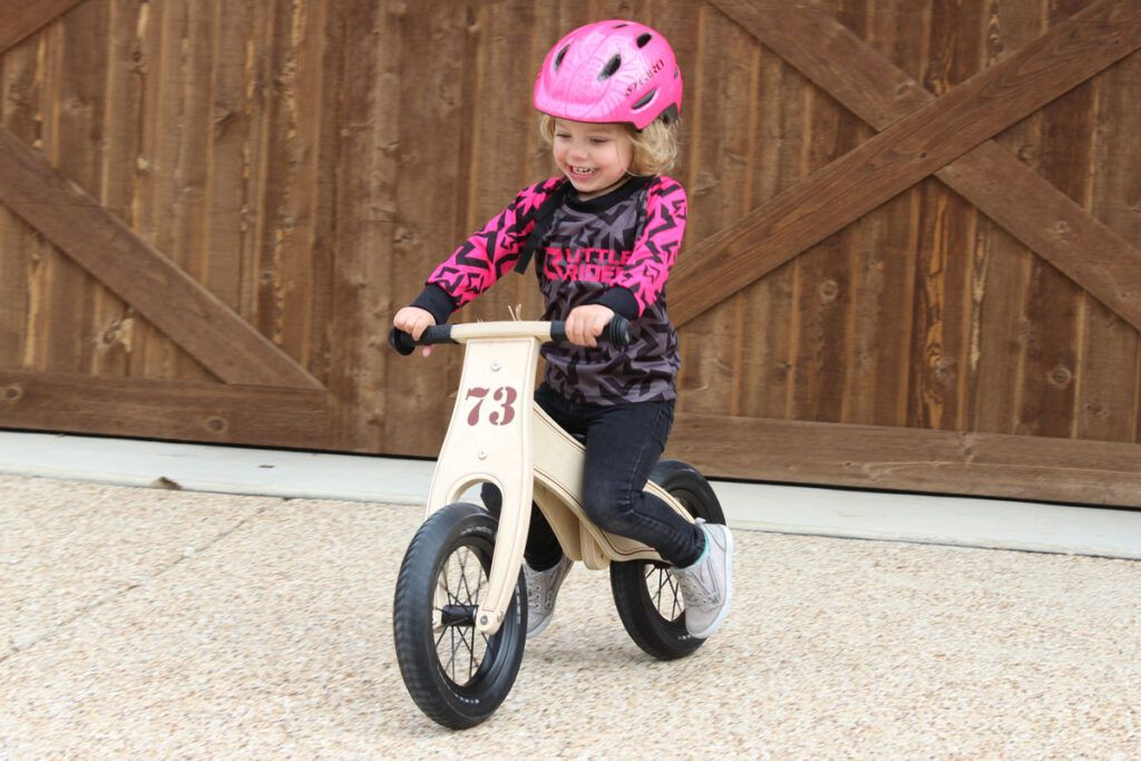 Toddler riding wooden balance bike and wearing a Little Rider Co bike jersey