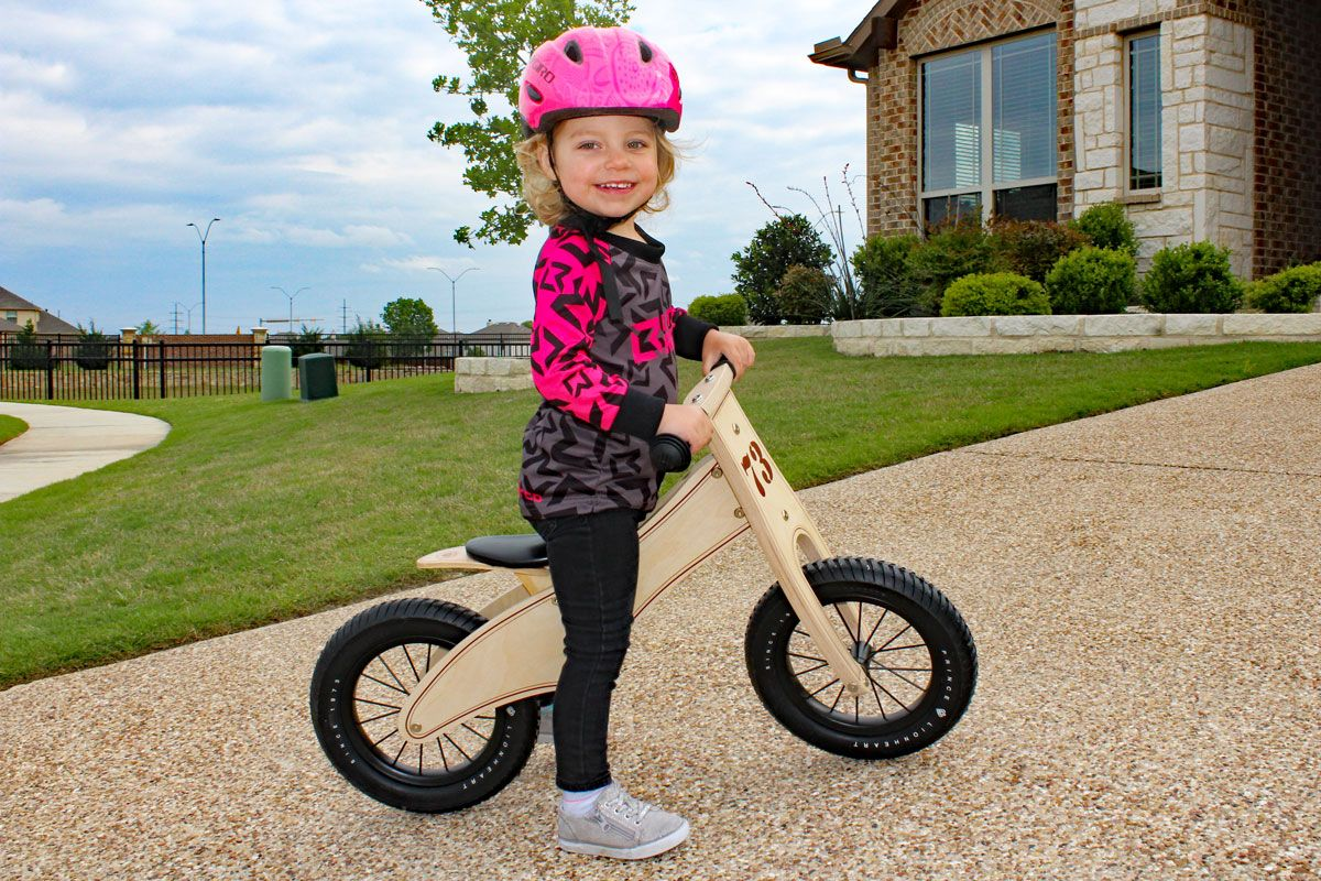 2 year old standing and smiling on Prince Lionheart wooden balance bike