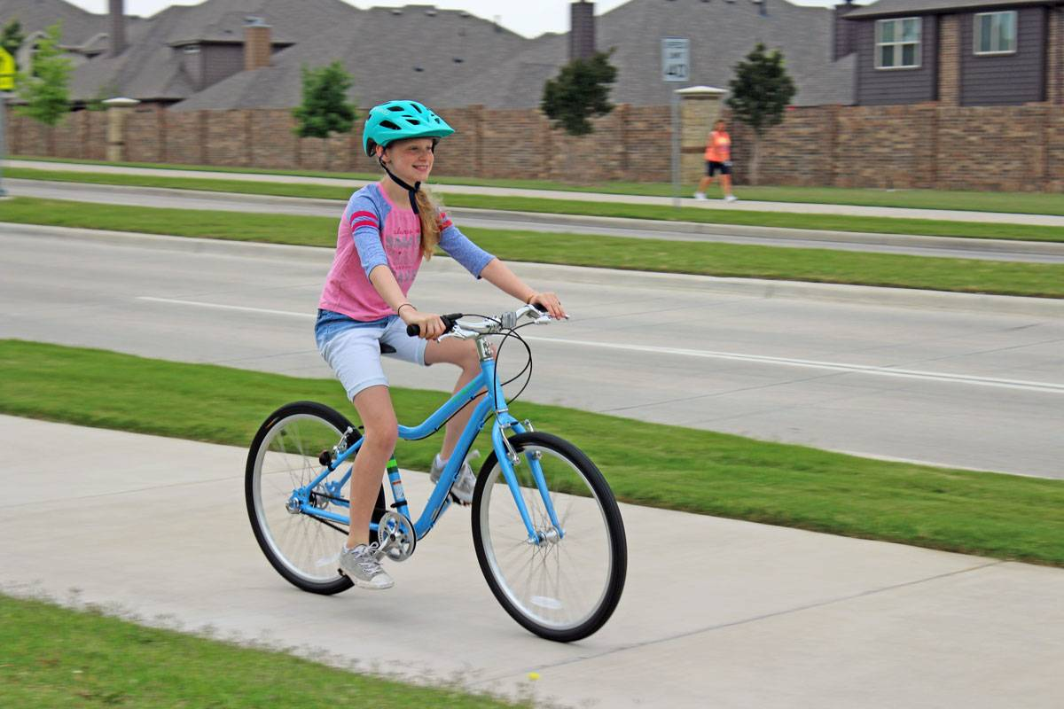 "10-year-old riding Priority Start 24"" kid's bike on a street sidewalk"