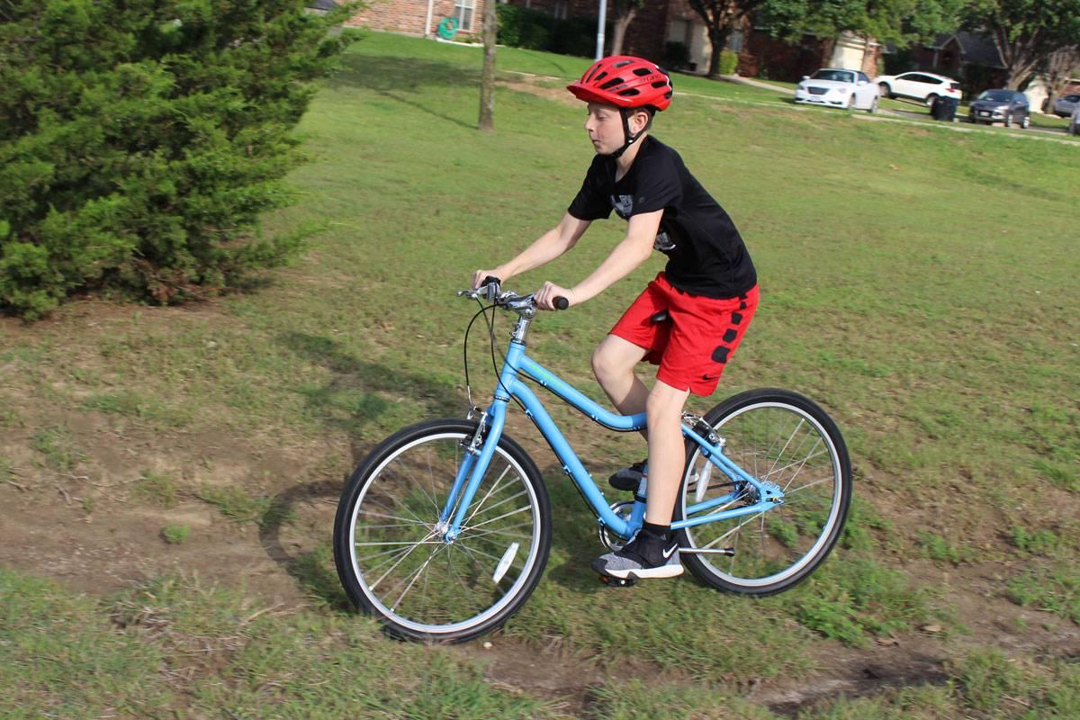 "12-year-old riding Priority Start 24"" kid's bike on a rough patch of dirt"