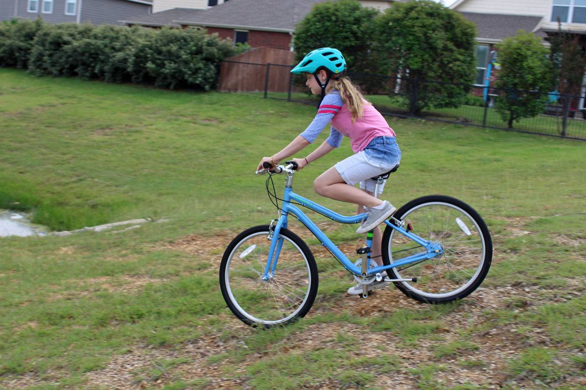 "10-year-old riding Priority Start 24"" kid's bike down a rocky and grassy hill"