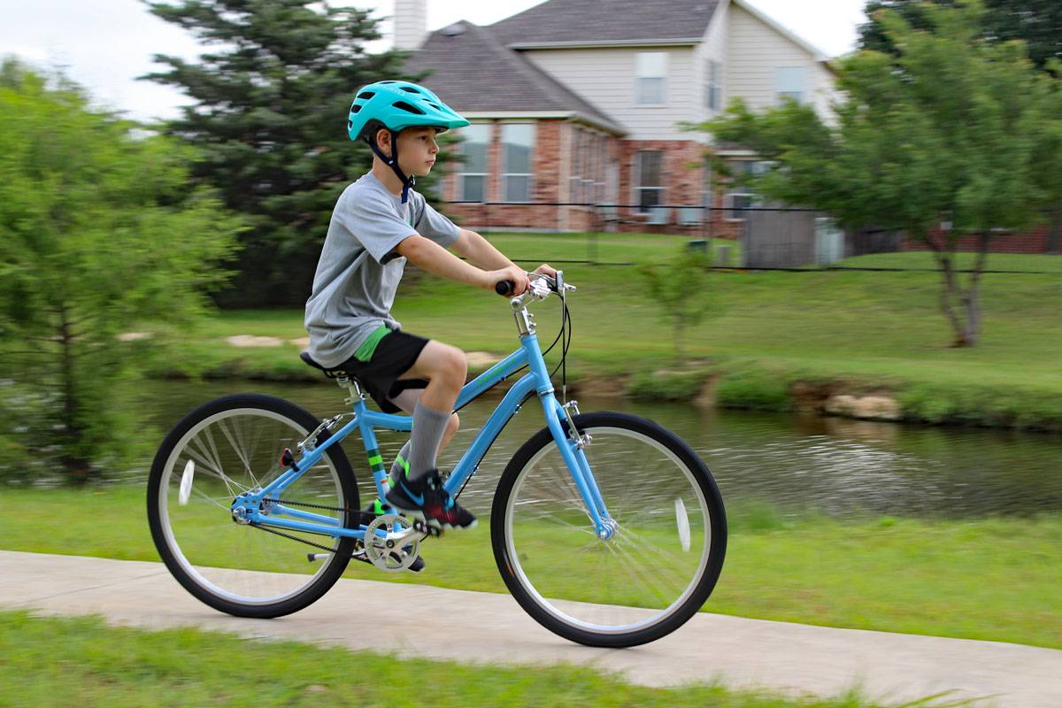 "8-year-old riding Priority Start 24"" kid's bike on a paved trail by a pond"