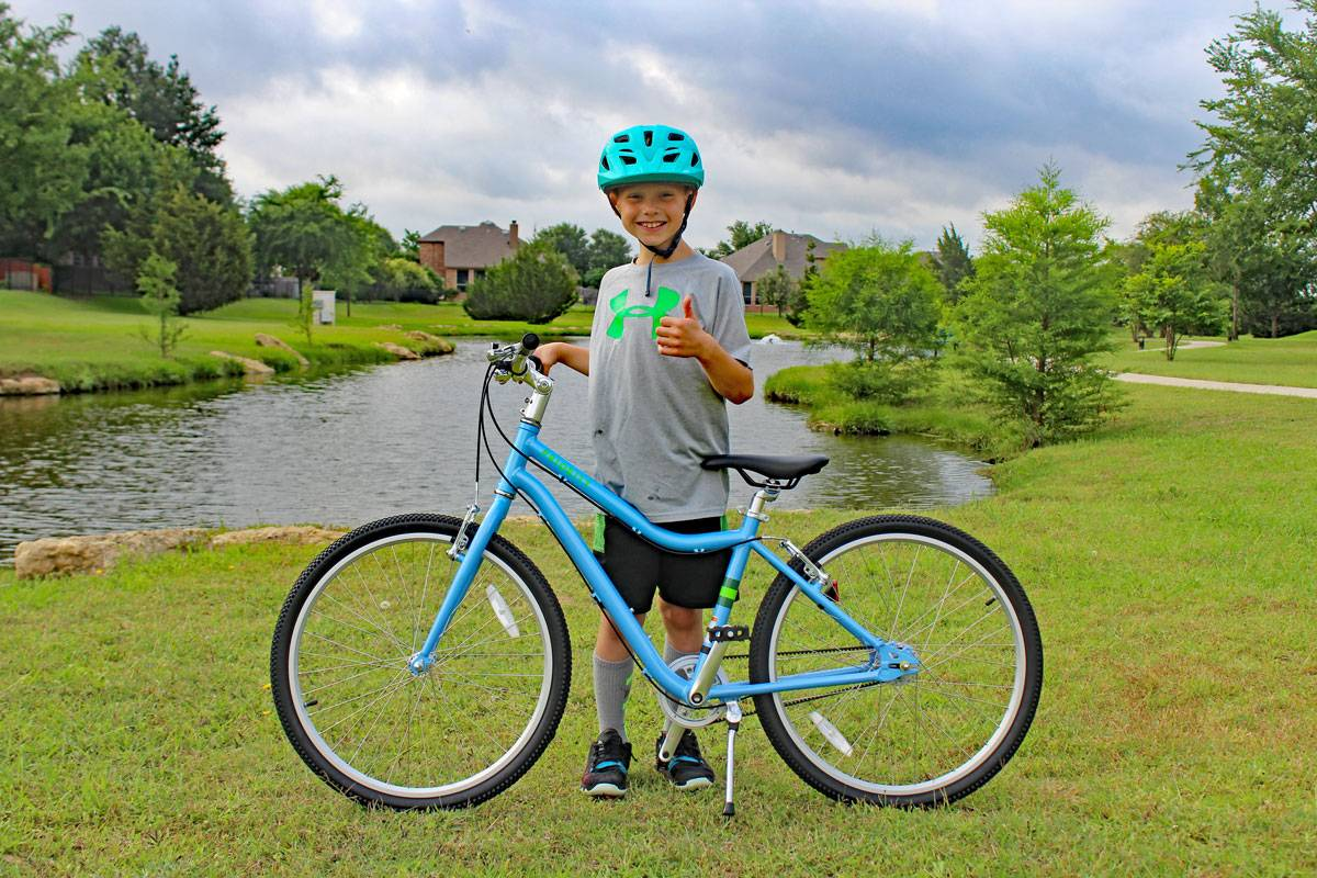 "8-year-old standing with his Priority Start 24"" kid's bike on a paved trail by a pond"