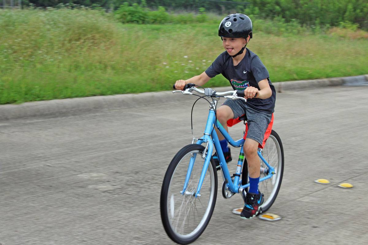 "8-year-old riding Priority Start 24"" kid's bike on the street in a bike rodeo"