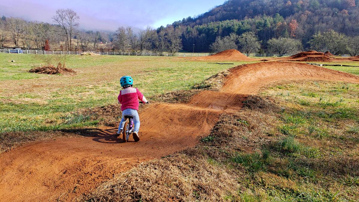 young toddler riding woom 1 balance bike on red dirt pump track.