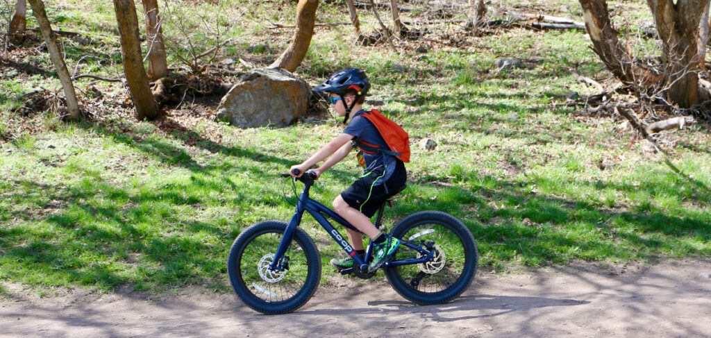 8 year old riding REI Co-Op Cycles REV plus 20 inch bike on mild trail