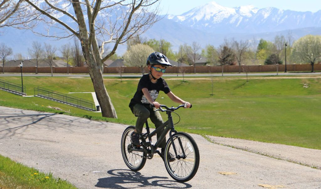 7 year old riding a boys 20 inch bike, a gray REI Co-Op single speed bike