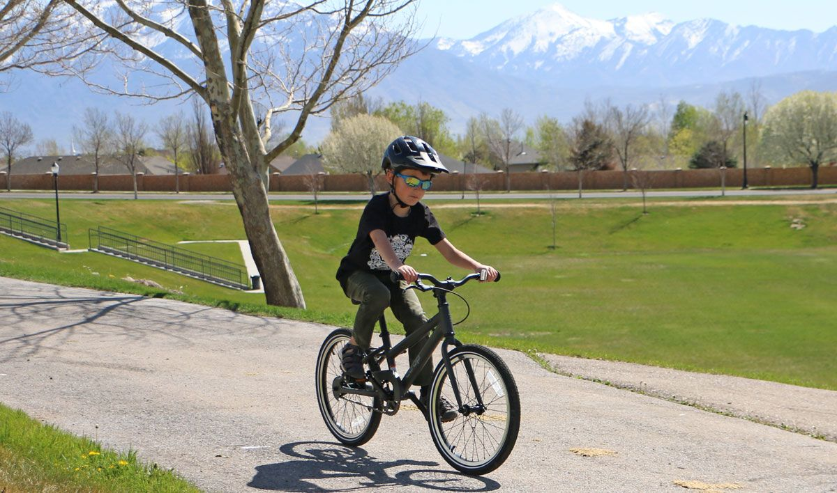Boy riding a REI Kids Bikes REV 20 inch single speed bike down a paved trail