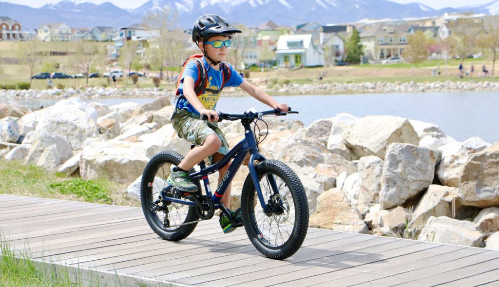 6 year old riding a REI Co-op boys 20 inch bike on a boardwalk