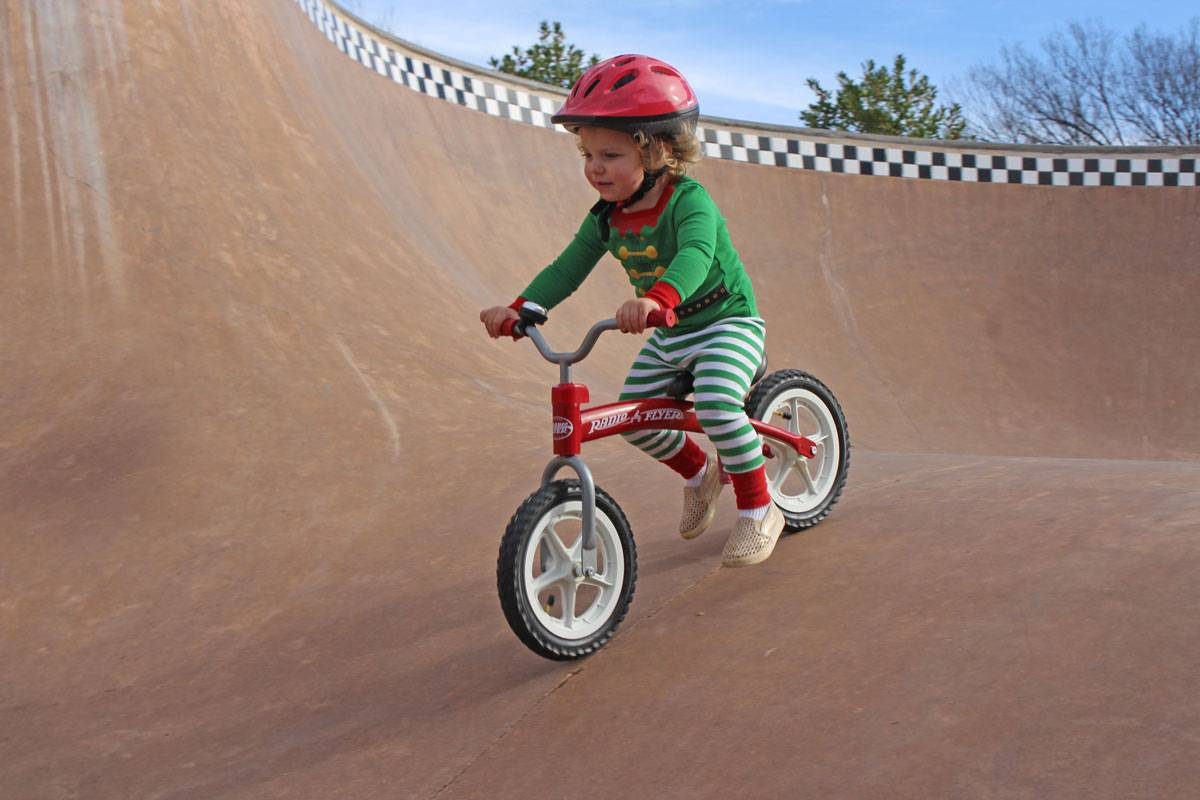 2 year old riding Radio Flyer balance bike down the ramp at a skatepark