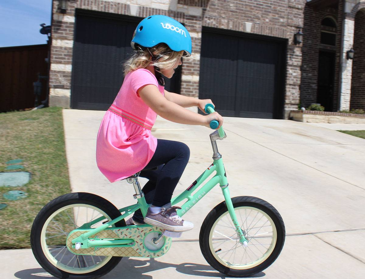 5-year-old girl riding Raleigh Jazzi 16 down sidewalk