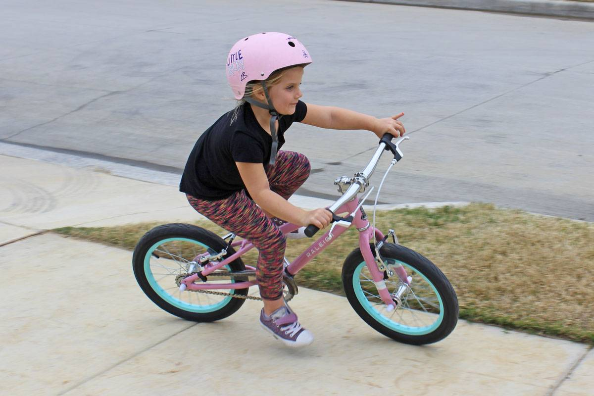 "5-year-old riding Raleigh Lily 16"" kid's bike, turning steeply into a curve"