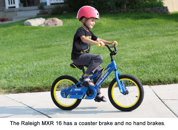 5-year-old boy happily riding the Raleigh MXR 16 on the sidewalk.