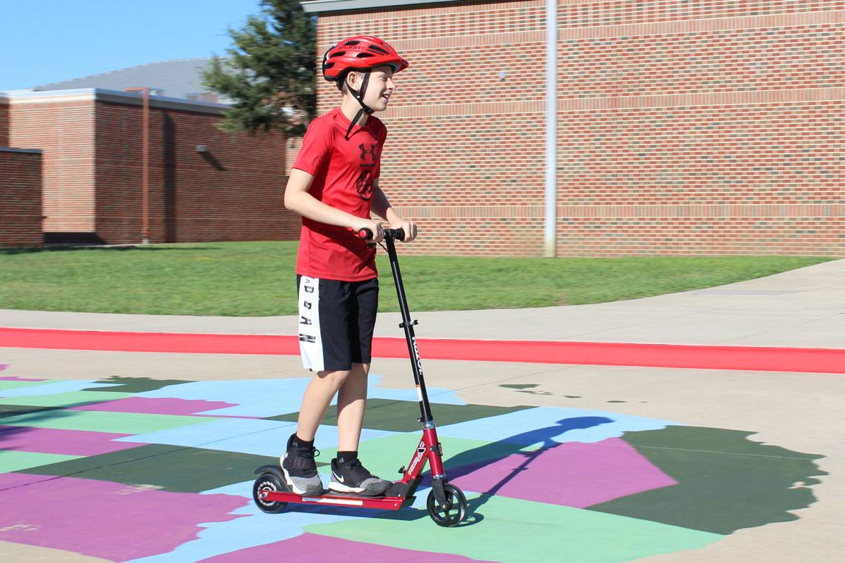 12 year old boy riding Razor Power A2 electric scooter on school playground