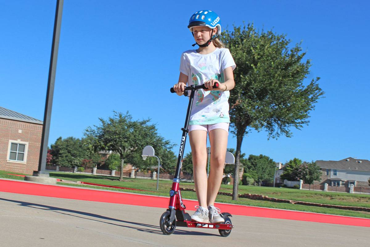 10 year old girl riding Razor Power A2 electric scooter on school playground