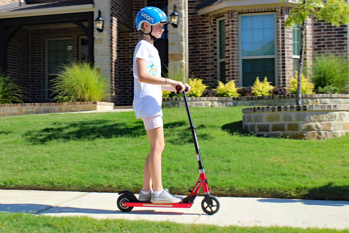 10 year old girl riding Razor Power A2 electric scooter in front of her house