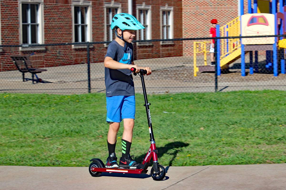 8 year old boy riding Razor Power A2 electric scooter on school playground