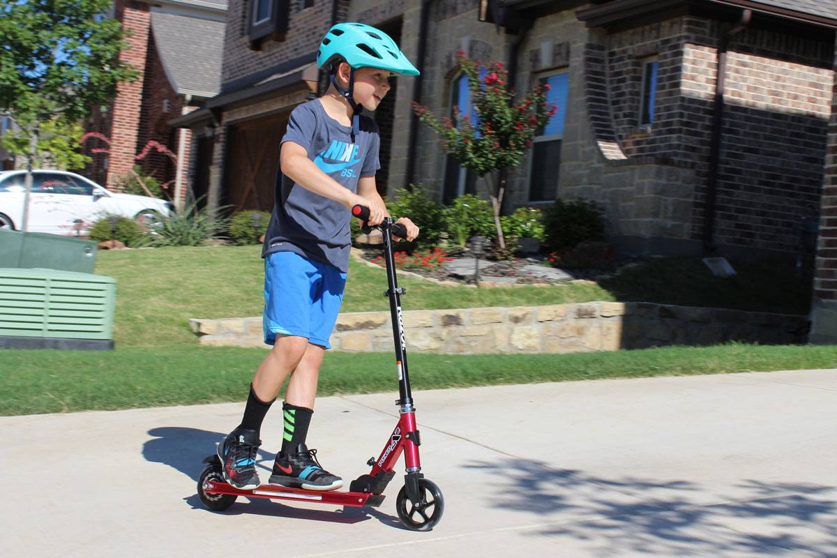 8 year old boy riding Razor Power A2 electric scooter in front of his house