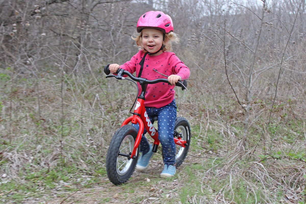 Toddler riding Ridgeback Scoot balance bike through the forest on a trail.