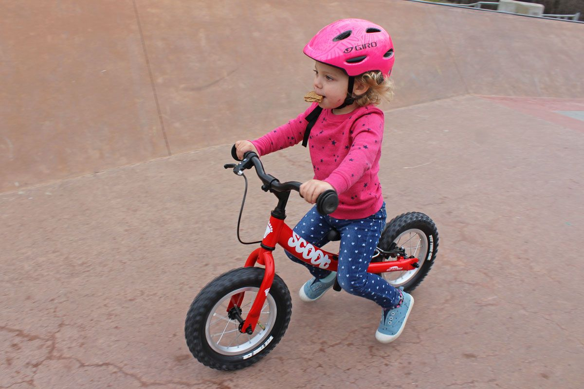 Toddler riding Ridgeback Scoot balance bike down a ramp at the skatepark while eating a cracker.