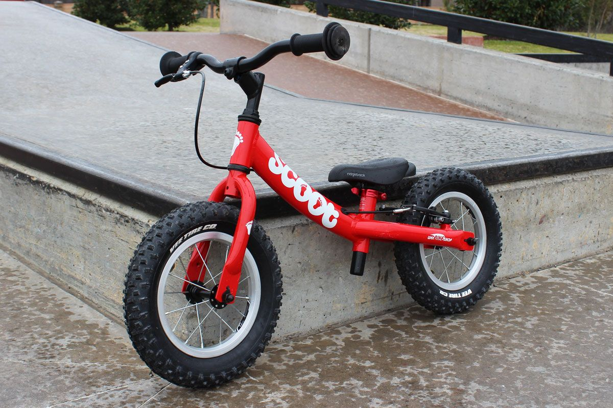 Ridgeback Scoot balance bike in red shown at the skatepark