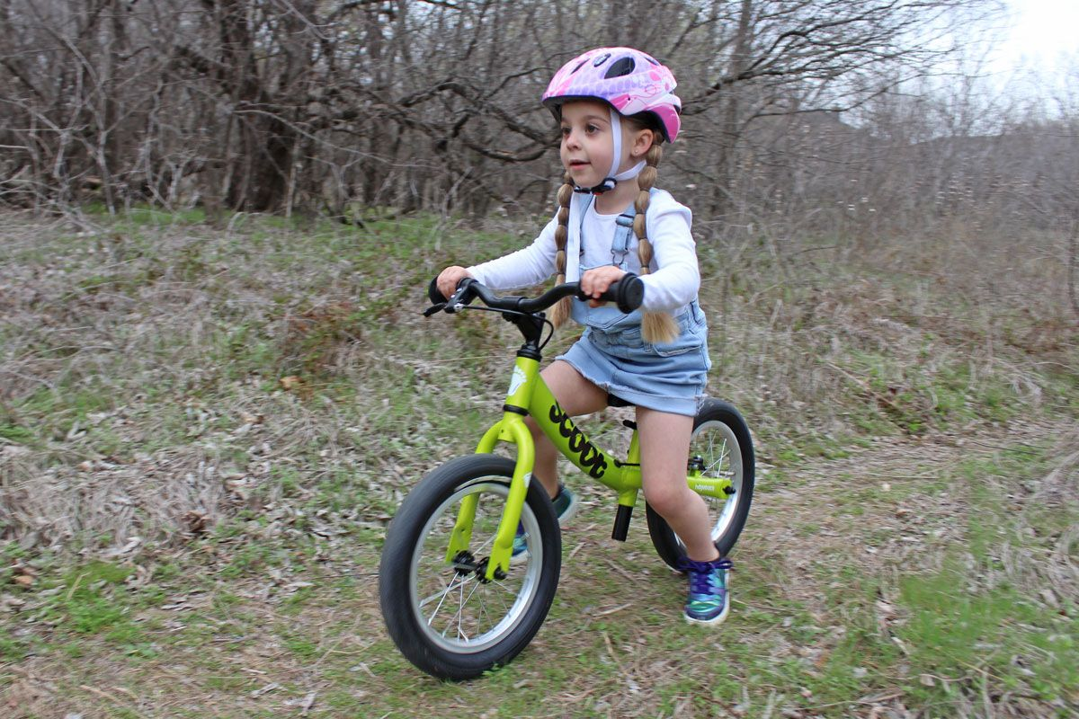 4 year old riding green Ridgeback Scoot XL balance bike through the forest