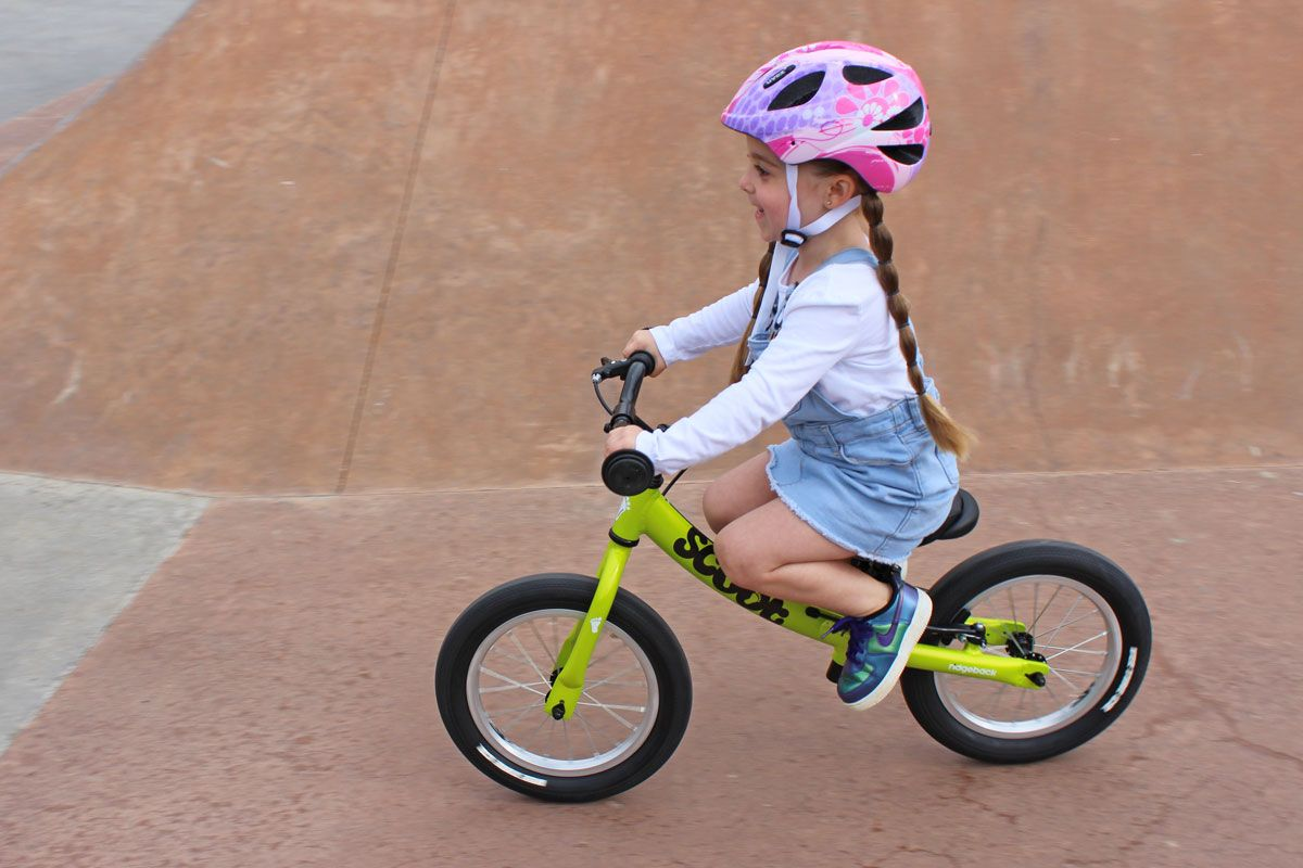 4 year old riding green Ridgeback Scoot XL balance bike at the skatepark, putting feet up on frame to glide