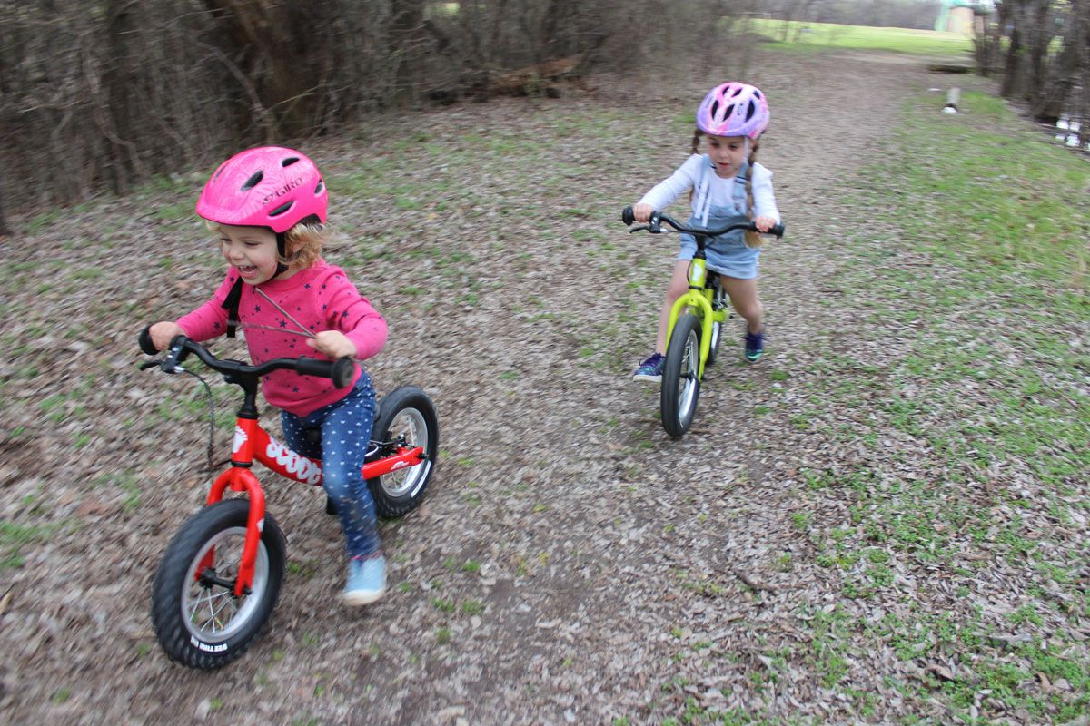 2 year old and 4 year old riding Ridgback Scoot XL balance bikes through the forest