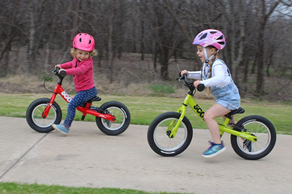 Two girls on balance bikes racing each other. A 2 year old is on the Ridgeback Scoot. The 4 year old is on the Ridgeback Scoot XL.