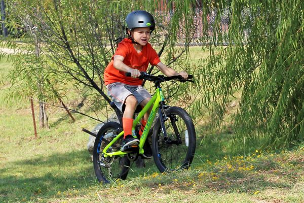 "Child riding up grassy hill on Raleigh Rowdy 20"" kid's bike in green"