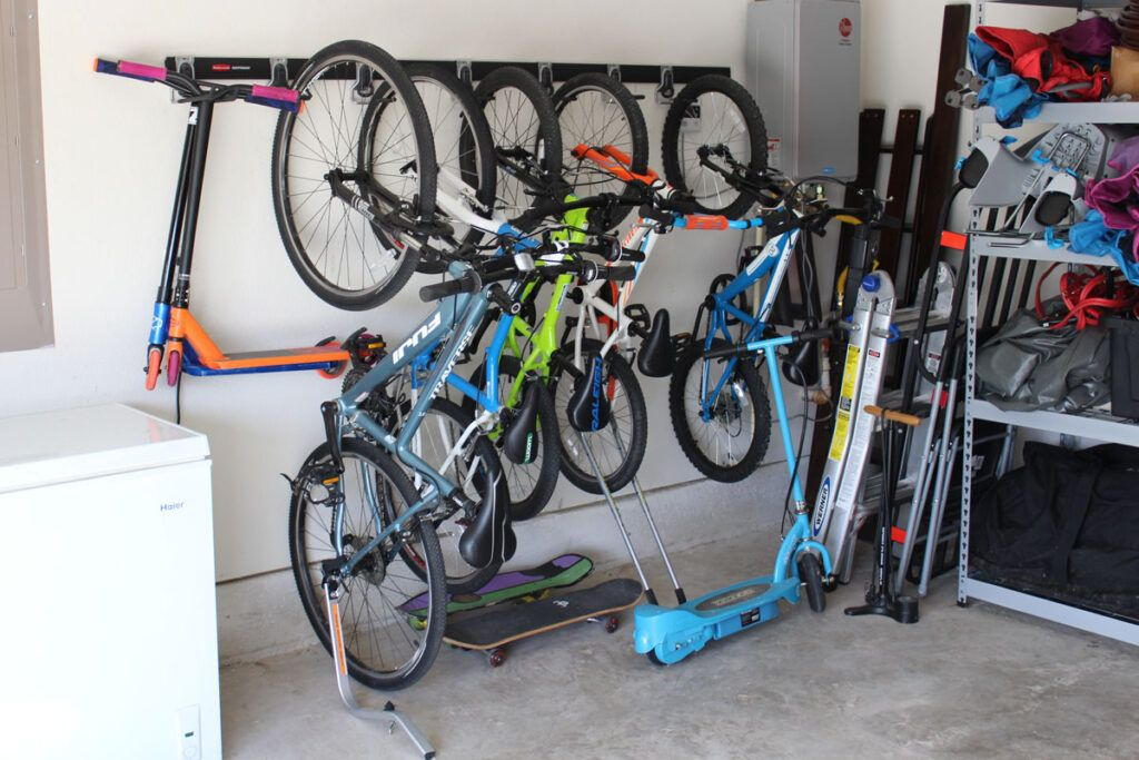 Rubbermaid FastTrack wall mounted bike rack filled with bikes and scooters in a garage