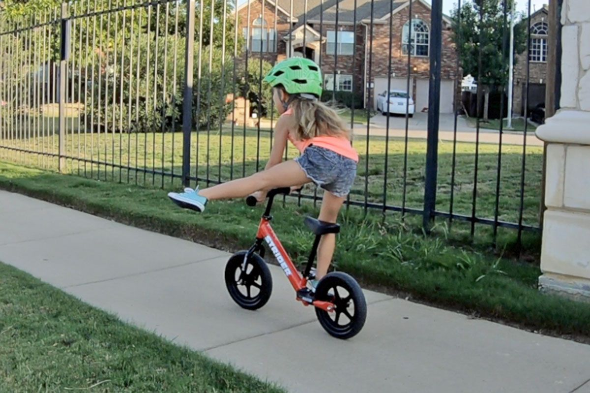 4 year old using the footrest on the Strider balance bike to stand up and point her leg out to the side