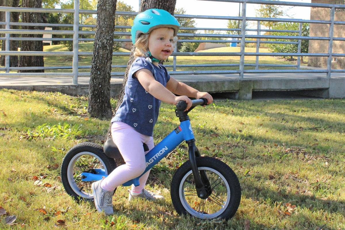 2 year old riding Swagtron K3 balance bike up ramp on grass