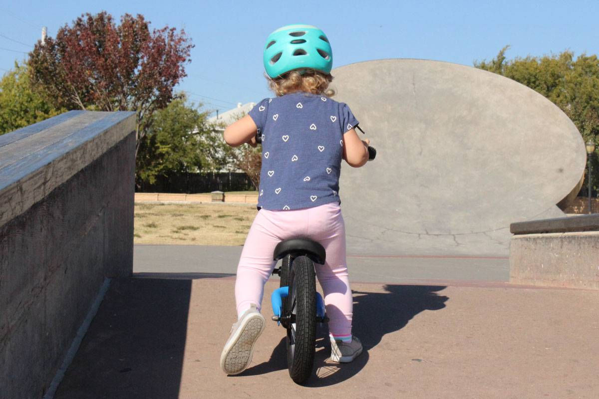 2 year old riding Swagtron K3 balance bike up ramp at skatepark