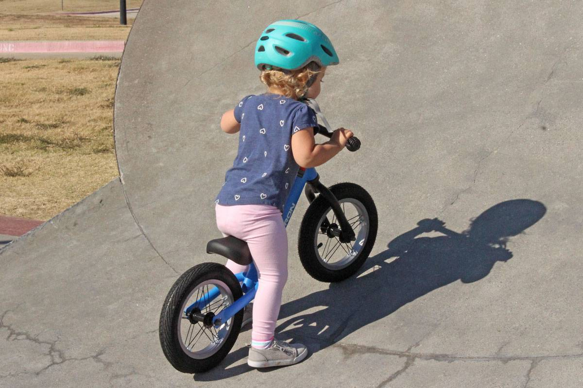 2 year old riding Swagtron K3 balance bike up feature at skatepark