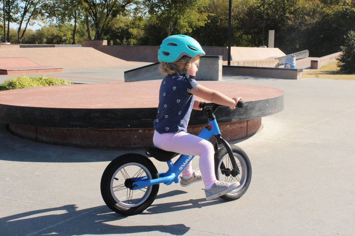 2 year old gliding on Swagtron K3 balance bike at skatepark