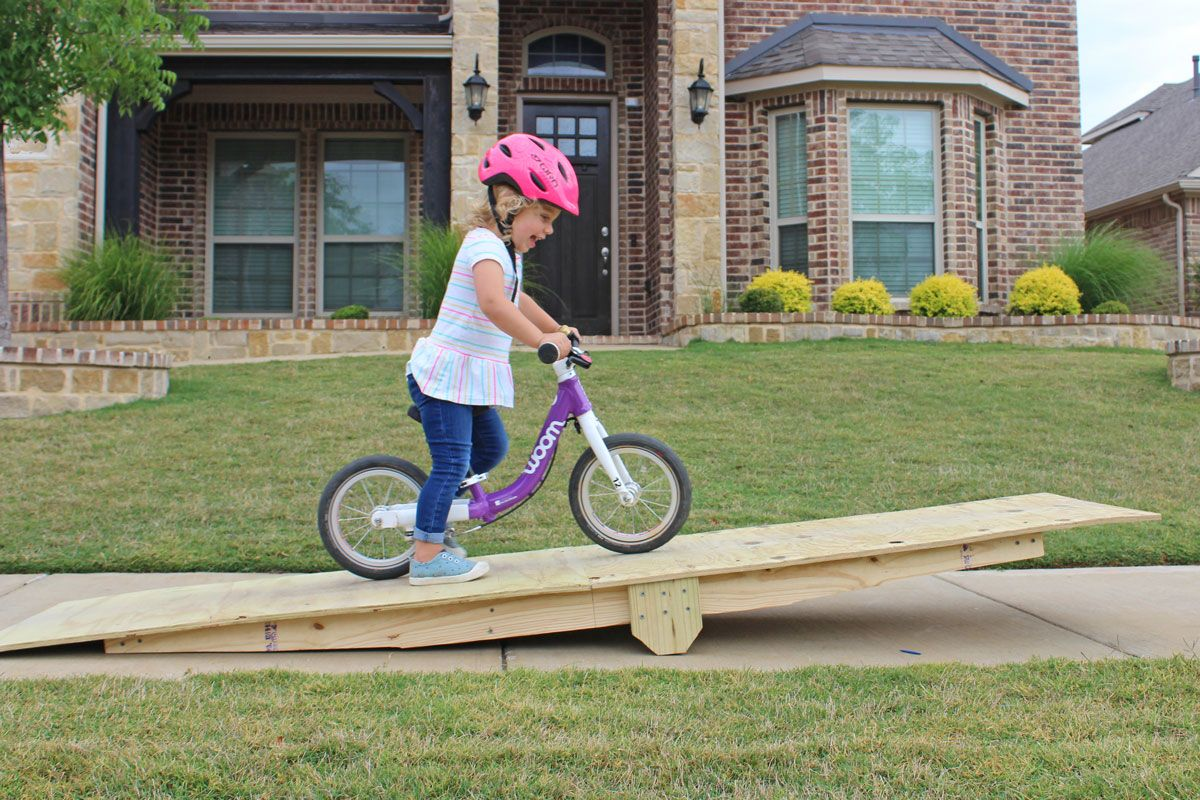 2 year old riding woom 1 balance bike on wooden teeter totter feature