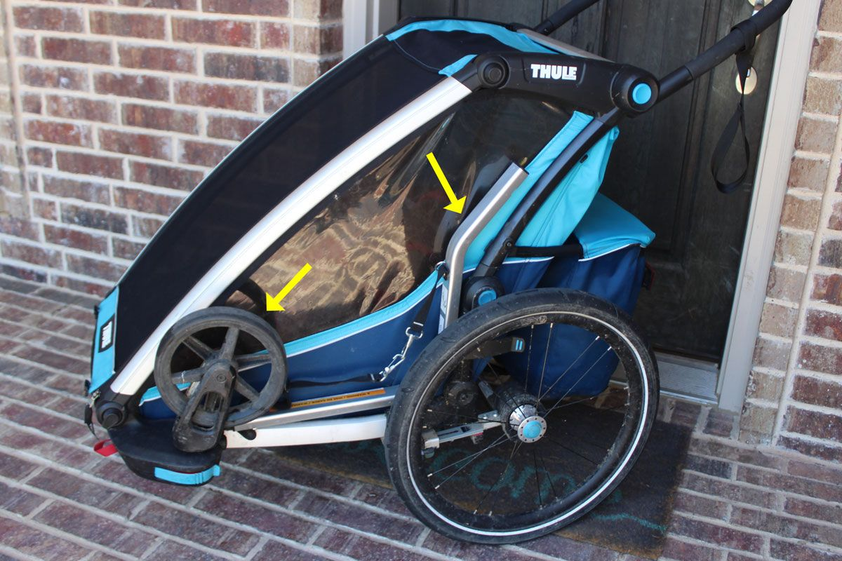 Side shot of Thule Chariot Cross showing stroller wheel and trailer arm stored on the trailer