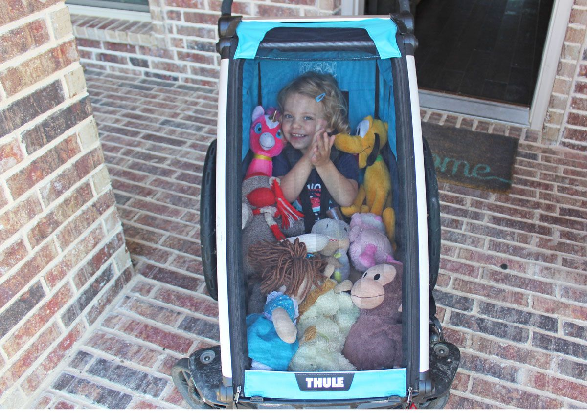 Toddler sitting in Thule Chariot Cross full of stuffed animals