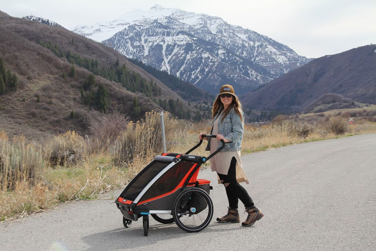 Mom with Thule Chariot Cross double stroller with mountain backdrop